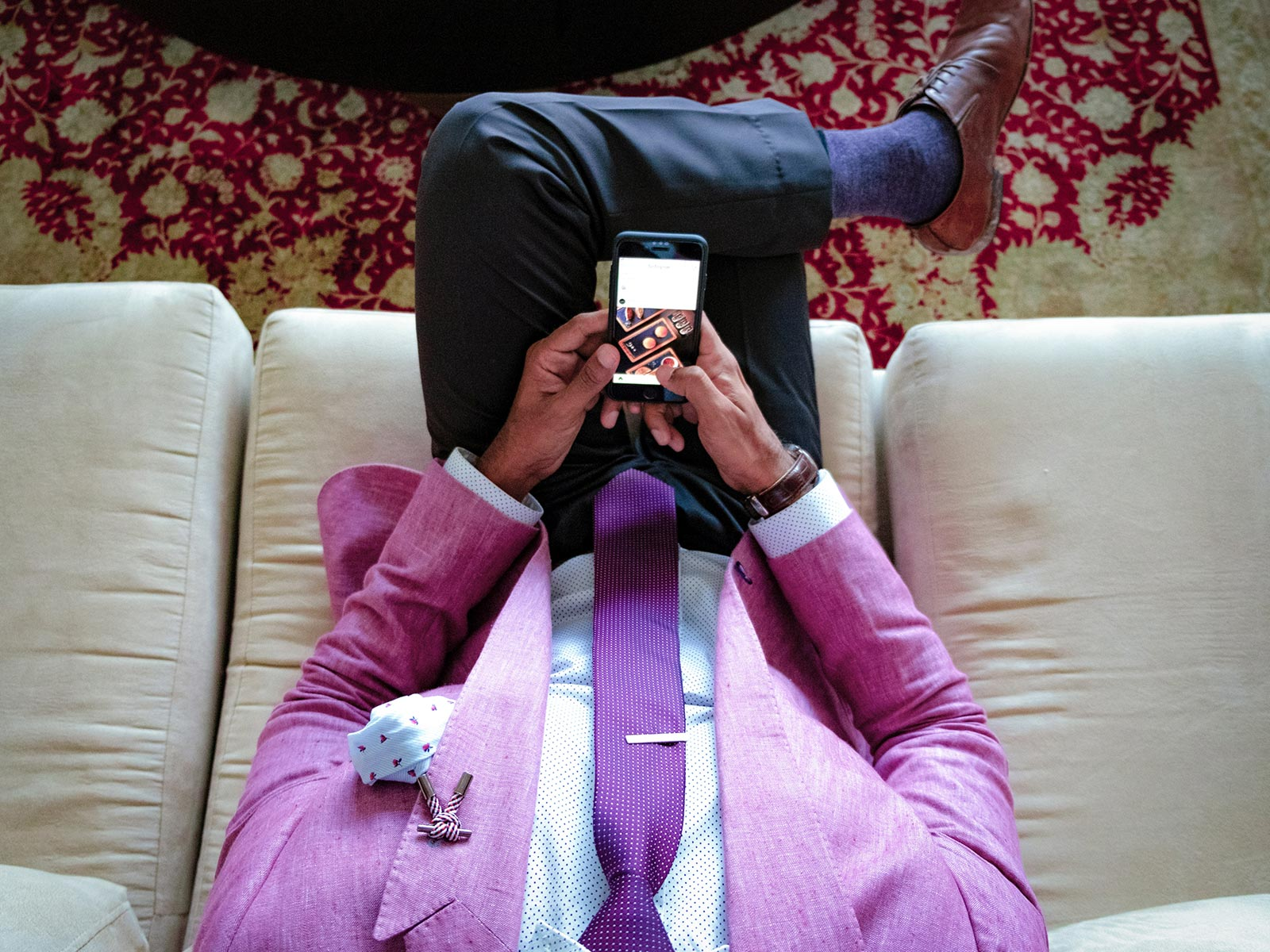 Overhead of man in pink suit on couch looking at phone