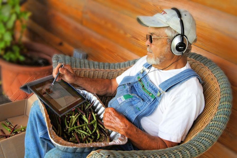 A farmer listens to audio with headphones while doing work.